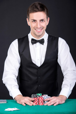 croupier: Portrait of a young croupier with gambling chips on the green table.