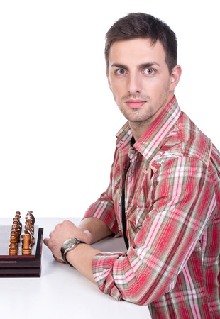 pawn adult: Portrait of a beautiful young man at the table with chess.