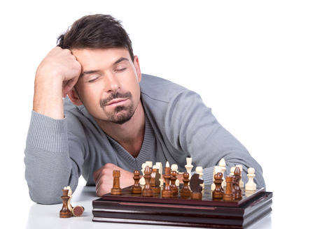 pawn adult: Portrait of a young sleeping man with a chess on a white background.