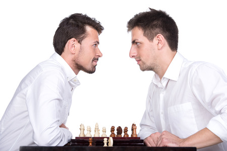 pawn adult: Portrait of two young men are playing chess on the white background and are looking at each other.