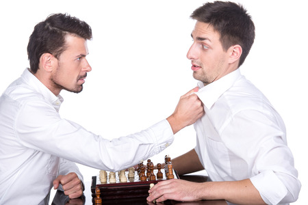 pawn adult: Portrait of two young man are playing chess on the white background. Should play by the rules.