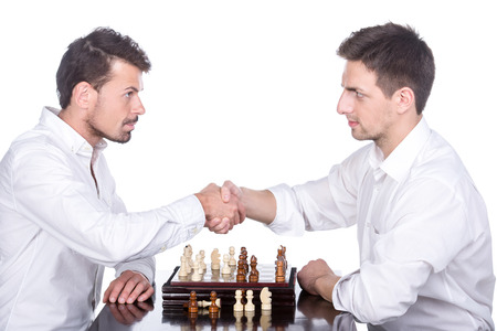 pawn adult: Shaking hands of two men are playing chess on the white background.