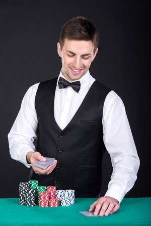 croupier: Portrait of a happy croupier is holding playing cards, gambling chips on table. Stock Photo