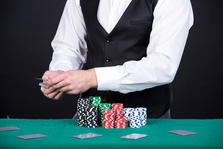 croupier: Portrait of a croupier is holding playing cards, gambling chips on table. Stock Photo