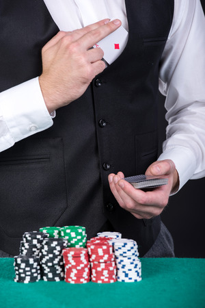 croupier: Close-up of a croupier is holding playing cards, gambling chips on table.