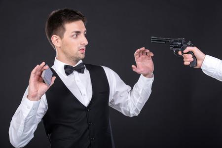 croupier: Portrait of poker croupier in casino. Someone threatening him weapons.
