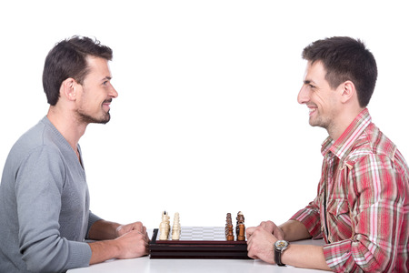 pawn adult: Portrait of two young man are playing chess on the white background.