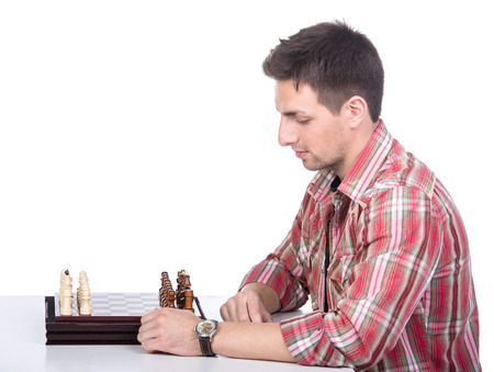 pawn adult: Portrait of a beautiful young man at the table with chess on the white background. Stock Photo