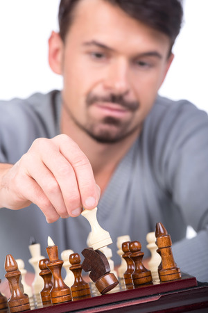 pawn adult: Portrait of man with chess is making the move on the white background.