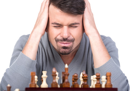pawn adult: Portrait of a young man with a chess on a white background. Closed his ears with his hands.