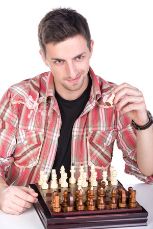 pawn adult: Portrait of a young man is playing a chess on a white background. Stock Photo