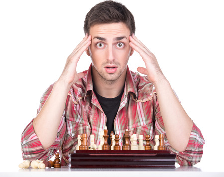 pawn adult: Portrait of young man is playing chess covered her face. He loses. Stock Photo