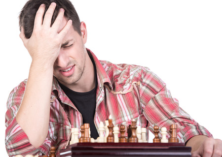 pawn adult: Portrait of young man is playing chess covered her face. He lost.