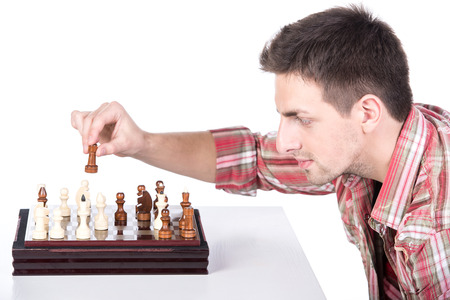 pawn adult: Portrait of a young man with chessboard is making a move.