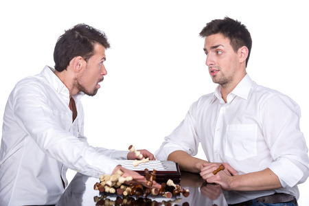 pawn adult: Conflict between two young men playing chess. On the white background. Stock Photo