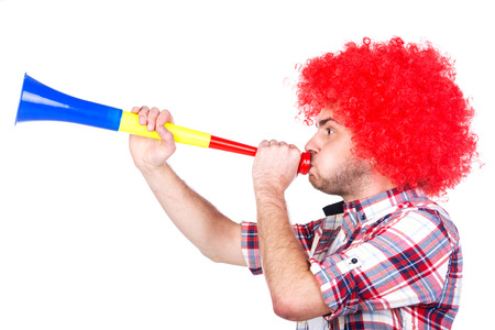 Portrait of football fan is blowing by vuvuzela, isolated on white.