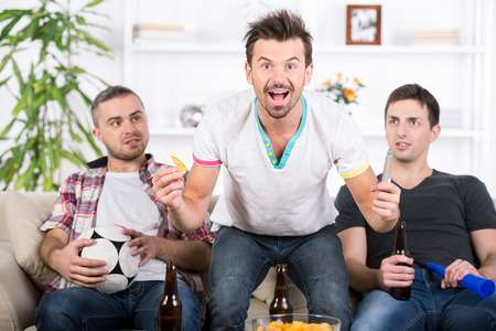 Three football fans are cheering football match at home.