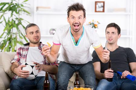 cerillos: Tres aficionados al f�tbol est�n animando partido de f�tbol en casa.