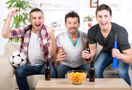 Opgewonden jonge mannen voetbal kijken thuis. Stockfoto