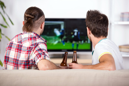 Rear view of two excited soccer fans are sitting on sofa and watching favorite team goal at tv. Stock Photo