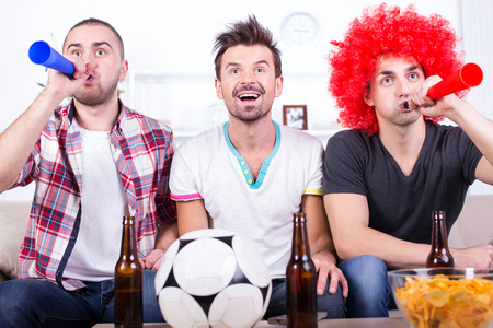Group of sports fans are watching game on TV at home. photo