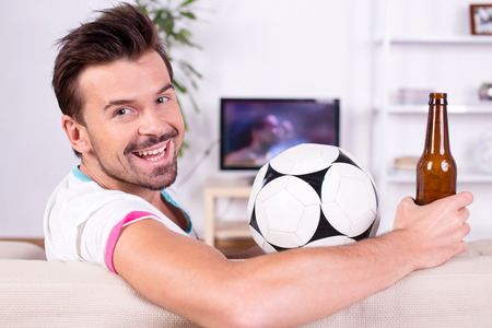 Smiling young man with soccer ball while watching the game. Looking at the camera.