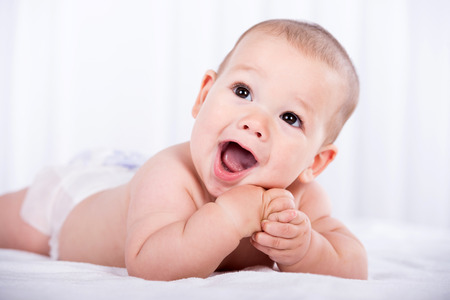 Portrait of a smiling crawling baby on the bed in the room. photo