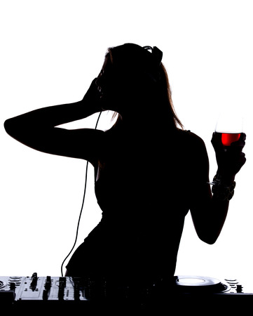 musician silhouette: Beautiful male DJ with her headphones is standing at her deck mixing sound.