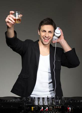 Portrait of a young smiling DJ standing at the mixer on a dark background. photo