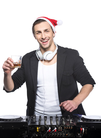 Portrait of a young DJ standing at the mixer in christmas hat on a light background. photo