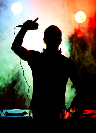 Silhouette of a young DJ at work with a microphone and the club lights on the background. photo