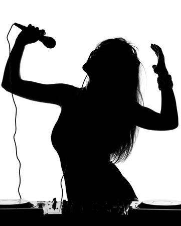 Beautiful busty DJ with her headphones, microphone is standing at her deck mixing sound. photo