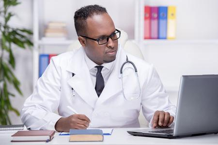 Retrato de un joven médico en el trabajo, está mirando el ordenador portátil. Foto de archivo - 33571170