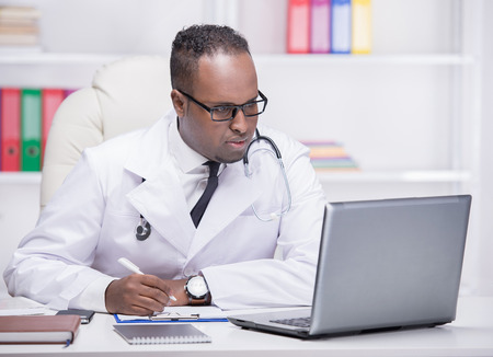 Portrait of young African American doctor at work, with laptop. photo