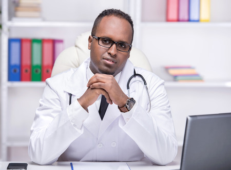 Portrait of young African American doctor is sitting in his office and looking at the camera. photo