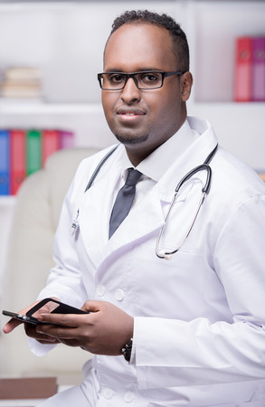 Portrait of young African American doctor with phone is looking at the camera. photo