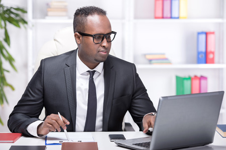 Businessman with laptop. Young African businessman is typing something on laptop in his office. photo