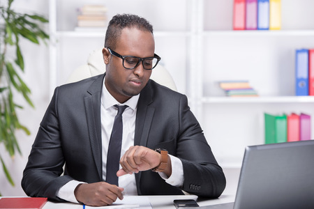 Portrait of young businessman at work, is pointing at clock. photo