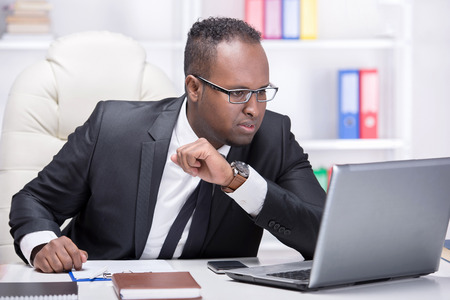 Businessman with laptop. Young African businessman is looking at laptop in his office. photo