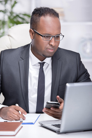 Portrait of young African businessman at work. He is looking at laptop in his office. photo