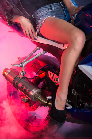 Close-up leg of an attractive woman biker is posing on motorcycle. Colored and foggy background.
