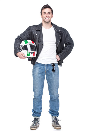 Portrait of a young motorcyclist is holding a helmet posing isolated on white background.