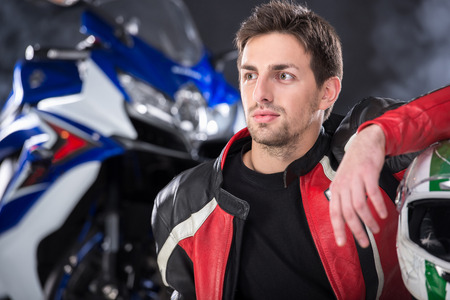 Portrait of young man with helmet. The motorcycle is on black background.