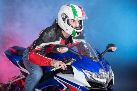 Motorrijder in apparatuur en helm op mistige achtergrond, zijaanzicht. Stockfoto