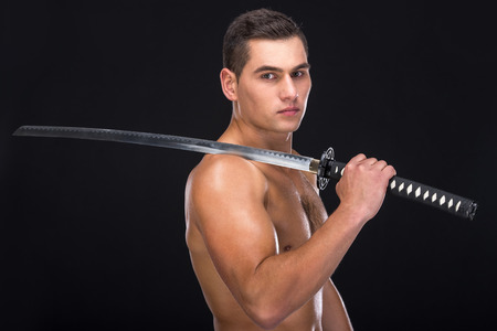 Portrait of a young muscular athlete with a sword on a black background. photo