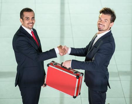 traslados: Dos hombres de negocios est�n agitando las manos y las transferencias de la maleta con el dinero.