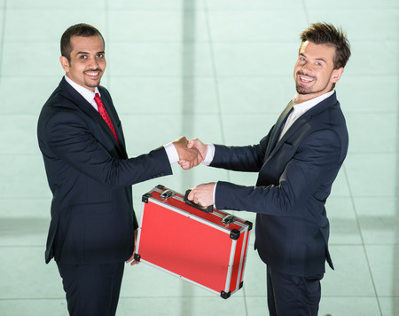 transfers: Two businessmen are shaking hands and transfers suitcase with money. Stock Photo