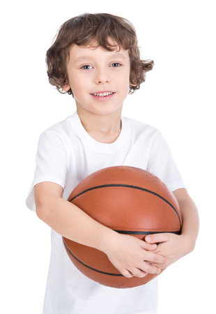 Portrait of a little boy with a basketball on a white background. photo