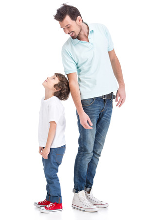 Portrait of happy father and his little son, on the white background. They are looking at each other.