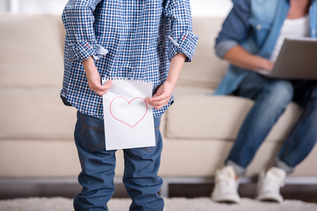 Boy is holding a paper with a picture of heart, against the background of a man sitting with a laptop. photo